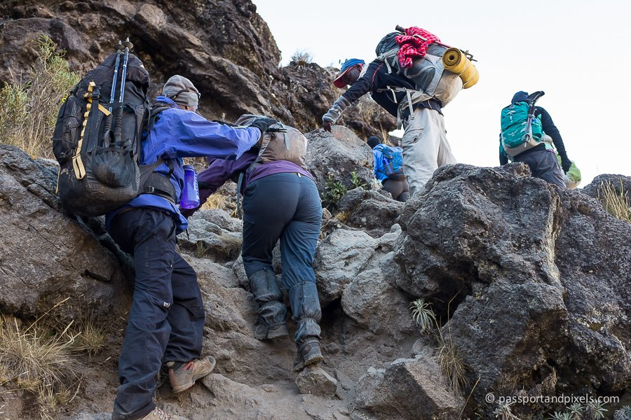 Four climbers scramble over rocks on the Barranco Wall, Kilimanjaro