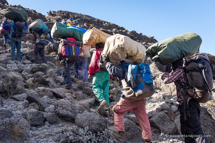 Porters carrying heavy gear up the Barranco Wall on Kilimanjaro