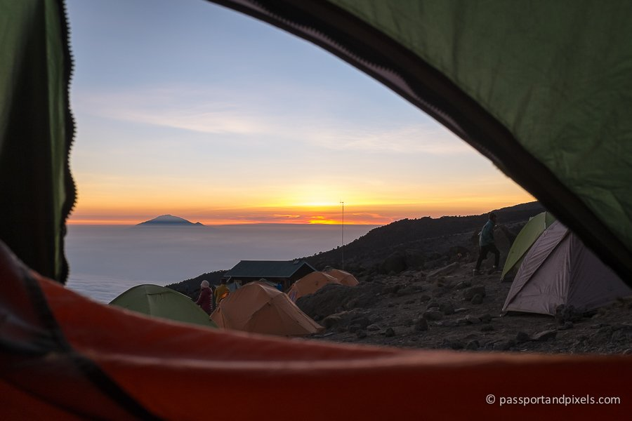 View from inside a tent on Mount Kilimanjaro, looking out towards Mount Meru sticking out above the clouds