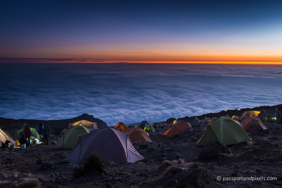Tents pitched on Mount Kilimanjaro at sunset, with thick clouds filling the valley below