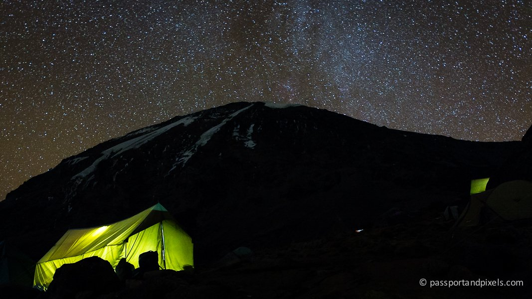 Mount Kilimanjaro at night, with a green tent lit up and a starry night sky overhead