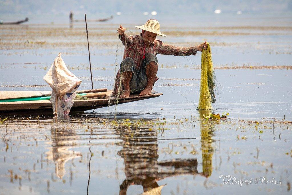A fisherman examines his net, Inle Lake, Myanmar