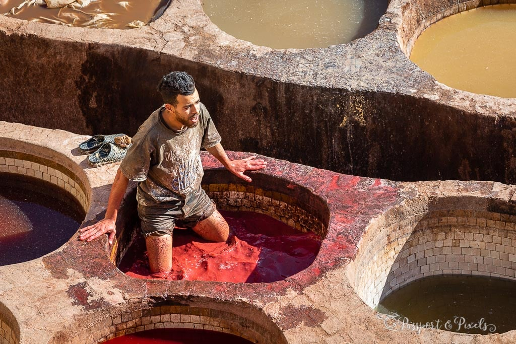 A worker mixes leather and red dye at Chouara Tannery in Fes