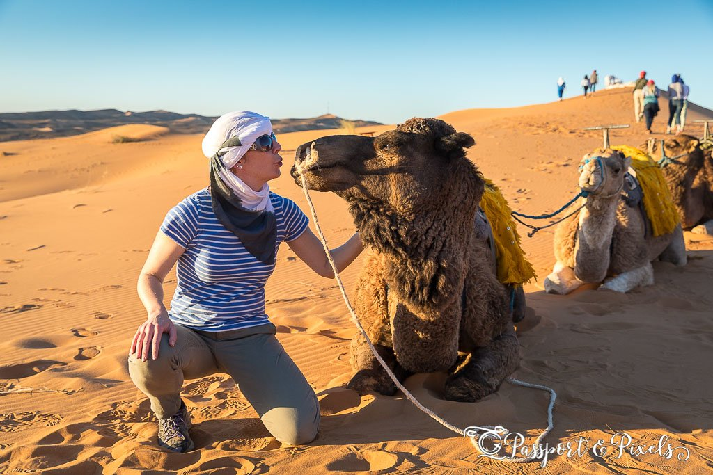 A woman kisses a camel in the desert in Morocco