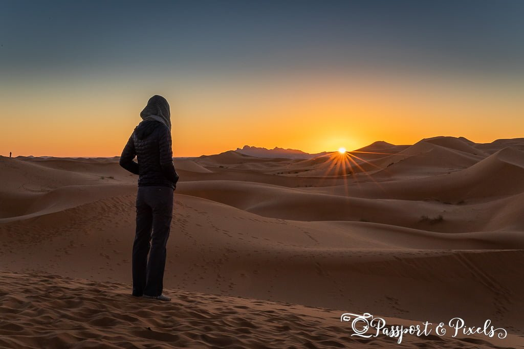 A woman watches the sunrise over the Sahara Desert, Morocco