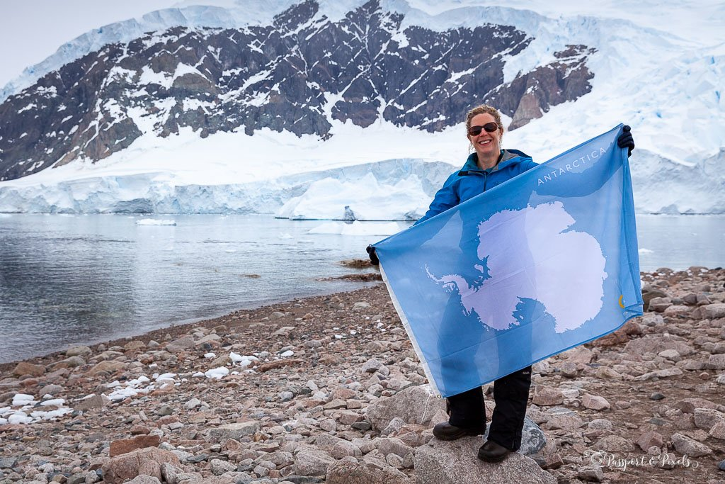 Holding the Antarctic flag in Antarctica, wearing waterproof clothes