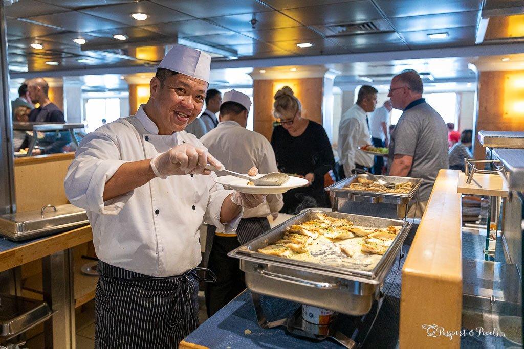 A chef serves fish in a creamy sauce on board Antarctica cruise ship Ocean Endeavour
