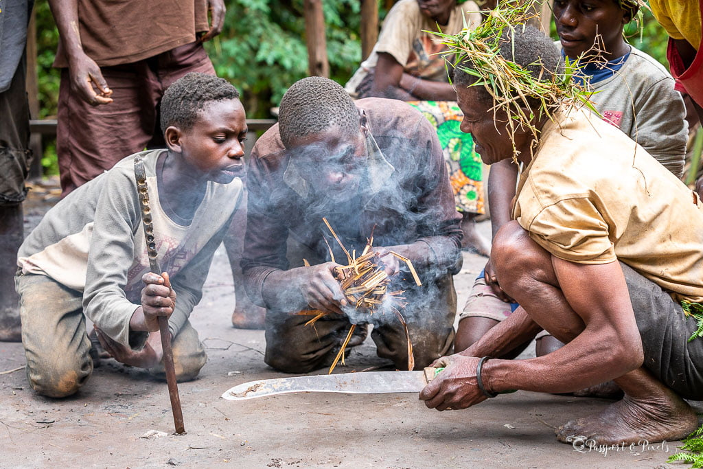A kneeling Batwa man blows on a collection of dry grass in his hands that smokes; to his left is a boy holding the stick that was used to create the initial spark by spinning.