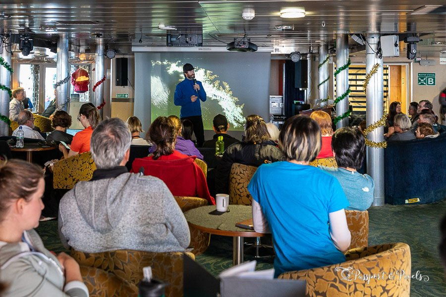 Passengers at a briefing on an Antarctic ship wearing casual clothes