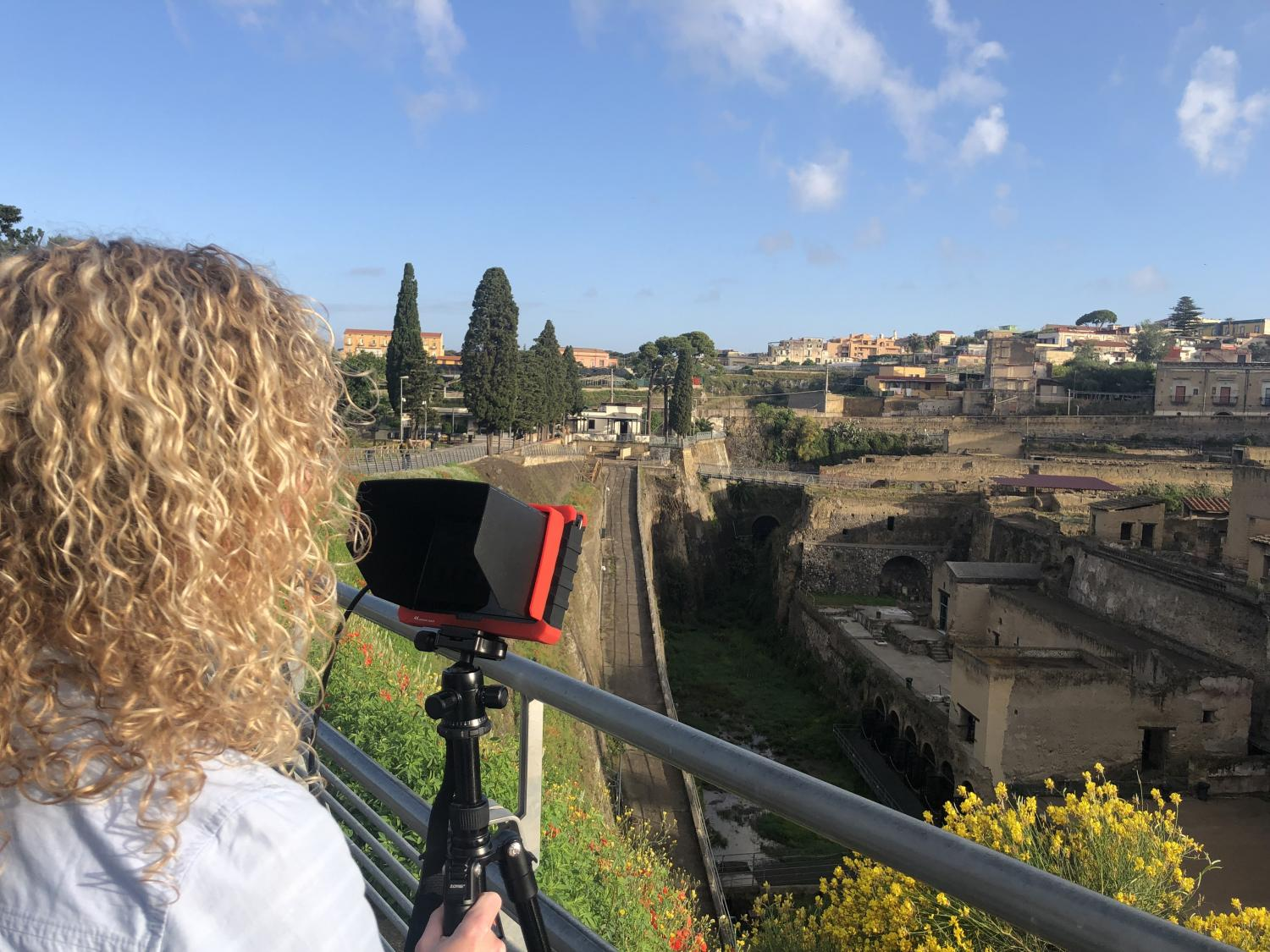 Watching the shot as the drone operator flies over the town of Herculaneum
