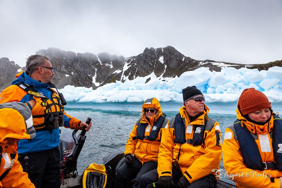 Tourists wearing Antarctic clothing including jackets, hats and gloves