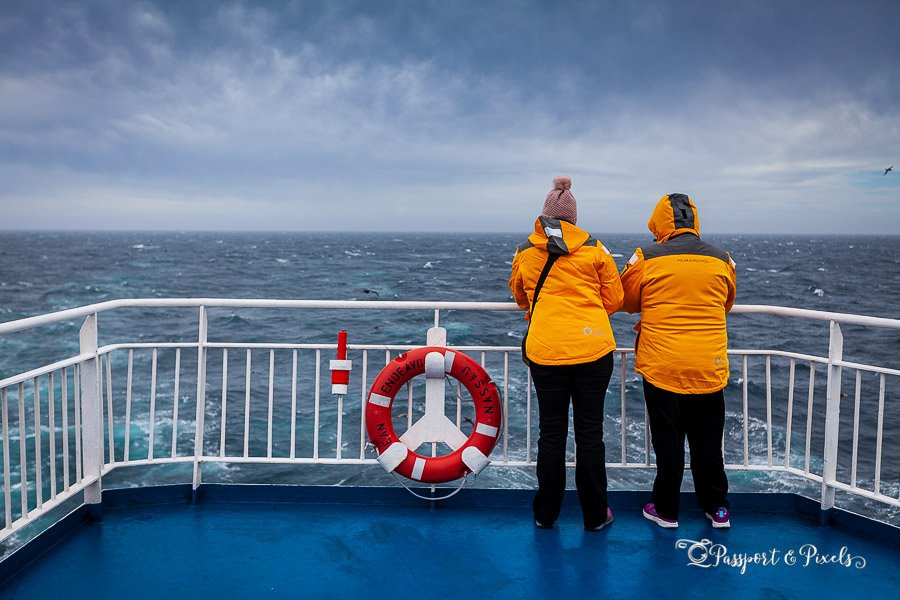 Two passengers in their Antarctic clothes looking out to sea
